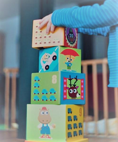 <alt=criança formando uma torre com quatro cubos empilhados>