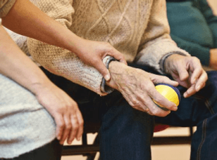 An elderly man holding a ball as he undergoes rehabilitation for a medical condition