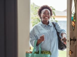 A smiling live-in self-employed carer opens the door to a client's home