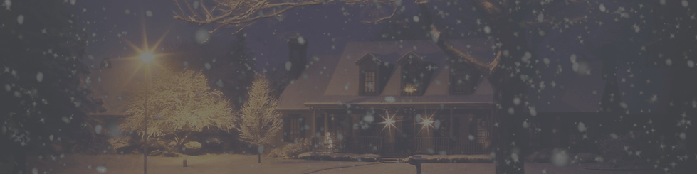 A country house at Christmas with light snow falling outside