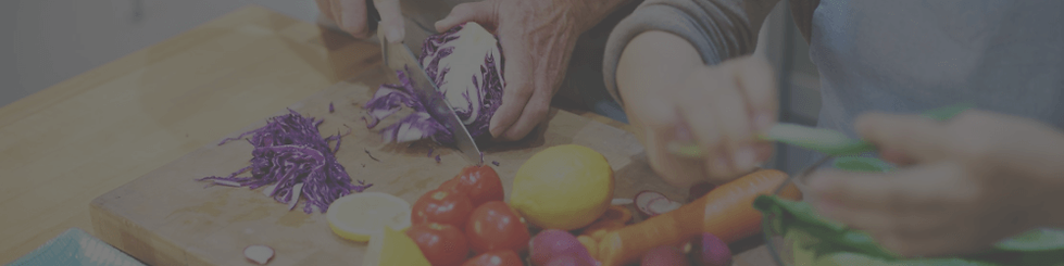 A live-in home carer helping an elderly male client chop vegetables in the kitchen having been matched by Country Cousins for their shared love of cooking