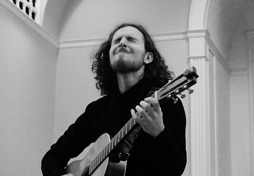 Maximilian playing guitar in his recital
