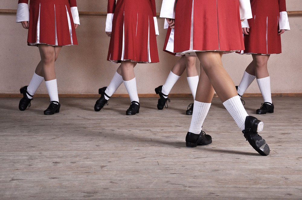 Group of young Irish dancers' legs in black dance shoes.