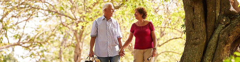 Two Boulder County elderly residents holding hands in the woods.
