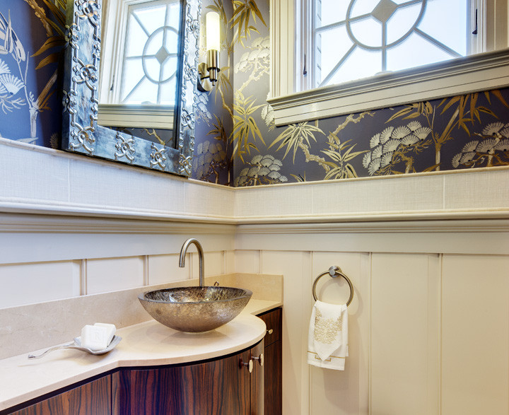 This powder room is made grand with a custom ebony Makassar cabinet and surface–mounted platinum blown–glass sink. Chihuly–inspired pendant chandelier adds drama while Italian wallpaper above the restored wainscoting offers warmth. Photo by Christopher Wesnofske