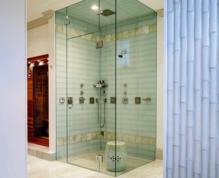 White travertine floors and Italian white-glass bamboo wall tile create a serene spa-like environment for this master bathroom. The shower has a fully integrated steam shower with linear drain and white onyx detail. Sauna built for two with integrated television. Photo by Christopher Wesnofske