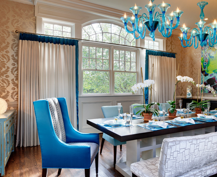 A contemporary twist on the traditional formal dining experience. Velvet and metallic damask wallpaper is accented with turquoise Murano glass chandeliers and turquoise–lined silk draperies. Benches, dining chairs and host/hostess wing chairs add interest while antique Chinese serving buffets add warmth. Custom dining table. Photo by Christopher Wesnofsk