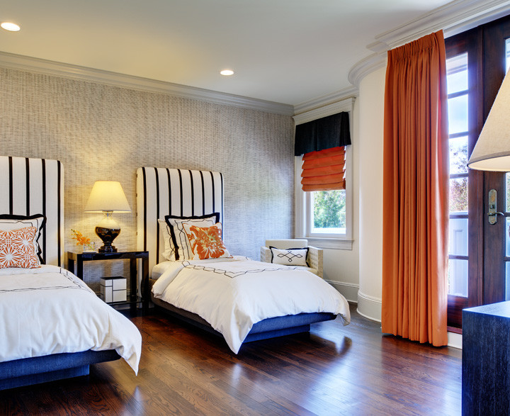 A guest bedroom designed with a neutral scheme and twin beds accommodates any variety of guests – from friends and children to grandparents. Custom upholstered headboards and black and white bedding adds tailored geometry; pillows and drapes add color. Organic woven black–and–white grass–cloth wall covering. Photo by Christopher Wesnofske