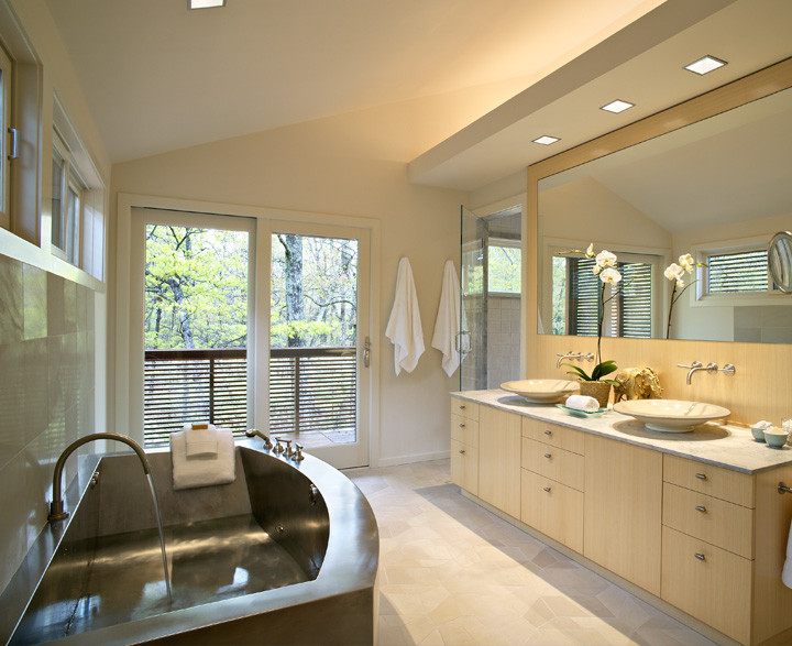 This room was designed for a busy executive couple wanting a space where bathing would rejuvenate the senses. A curved stainless steel tub adds contrast against the natural wood wall opposite. Soothing river rocks line the shower floor. Two ceramic sinks resemble Japanese rice bowls. Photo by Christopher Wesnofske