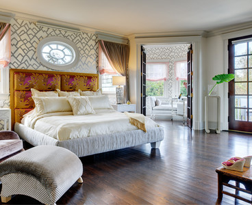 Each window in this master bedroom is equipped with blackout shades to block out bright morning sun. The octagonal sitting room features a chaise lounge for two to sit and read. White mother–of–pearl nightstands and silver table lamps pull from the silver accents of the hand–block–printed paper on the walls. Photo by Christopher Wesnofske