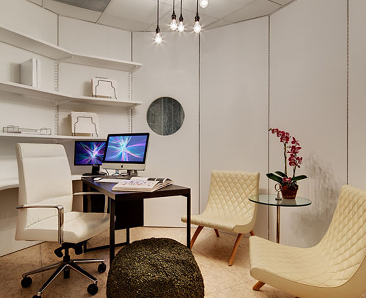 """Desk, chairs, table and a textured, crunchy ottoman form a """"sculpture"""" in the middle of this multi-sided office—complete with porthole. Furniture gets moved around as a team is called in to brainstorm. A wonderful, kooky environment for the creative mind. Photo by Christopher Wesnofske"""