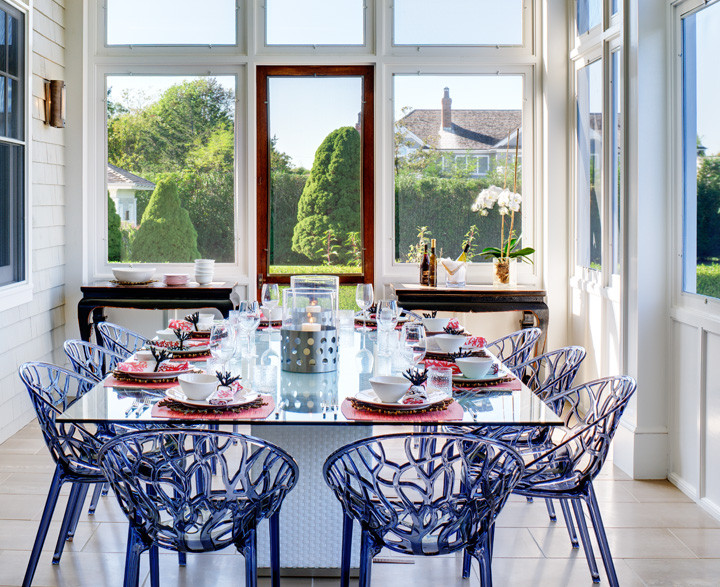 This screened-in porch combines practicality and visual harmony with resin dining chairs, wicker and glass–top dining table, and steel/glass hurricane lamps. Floors are a durable olive stone while the ceiling is painted ice blue to deter bugs from nesting. An elegant setting for a summer dinner party. Photo by Christopher Wesnofske