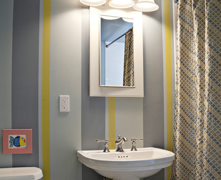 This is how to take a classic Hamptons cottage bathroom and freshen it for a young child. A playful cabana effect was created on the walls by a faux artist while the original tile floor was retained to respect the home's history. Photo by Genevieve Garruppo