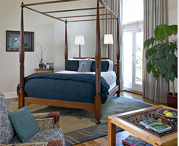 With a preference toward British Colonial, this client wanted a bedroom with a masculine feel. An angled bed adds drama and provides a sightline to the entryway, giving command of the door. The console behind the headboard offers lighting for the bed and for the entrance to the balcony. Photo by Christopher Wesnofske