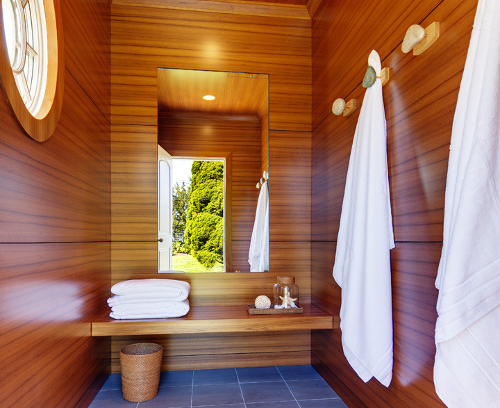 This outdoor poolside changing room is convenient for guests and keeps wet swimsuits (and feet) out of the house. Floor–to–ceiling solid teak paneling with river rock towel hooks, inlaid mirror and floating teak changing bench. Floor is an indoor/outdoor porcelain tile. Photo by Christopher Wesnofske