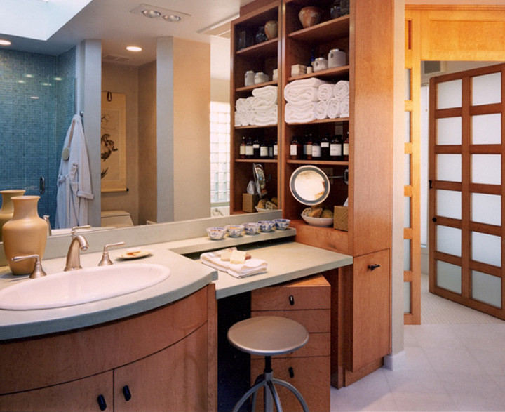 A new entrance created with a Shoji door and wall adds space to this bathroom. A small corner – featuring a roll–about makeup dresser and stool, a shelving unit for towels and accessories, and a hamper neatly tucked into the cabinetry – does the work of a much larger bathroom. Photo by Christopher Wesnofske