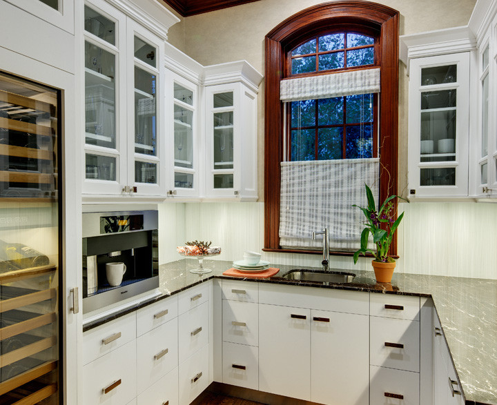 This butler's pantry is as beautiful as it is functional. Custom cabinetry matches the kitchen and offers an eye–pleasing contrast against a white backsplash. Equipped with a full–sized wine refrigerator and built–in coffee machine, dishwasher and water filtration system. Photo by Christopher Wesnofske
