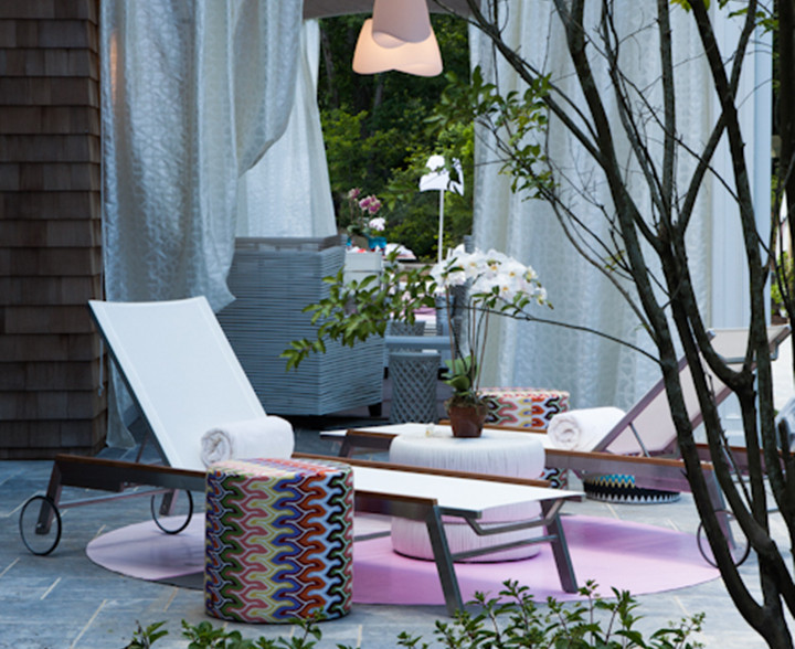 Dusk is a favorite time of day in the Hamptons. Visualize taking time out, reading, lounging, or just sipping a martini. The round rug, hand-painted by Rory Conway, adds refreshing energy to the space. Missoni table; lounge chairs from Tui Lifestyle. Photograph by Peter Dressel
