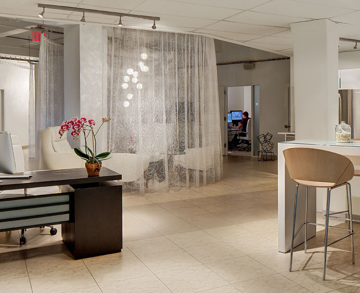The bright, white, open space defines Light of Day and provides positive business energy. A bittersweet chocolate reception desk (with modesty panel) contrasts with the white décor, so it's clear it is the reception area. Oversize vinyl tile floor pick up the rhythm of the business as feet travel the office space. Photo by Christopher Wesnofske