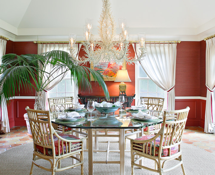 The conversation starter in this Hamptons dining room is always the grand iron chandelier, which looks like it was dipped in kosher salt. The repartee continues around the octagonal table designed to gather friends and family close together. Round sea–grass rug and red grass–cloth walls add warmth and energy. Photo by Christopher Wesnofske