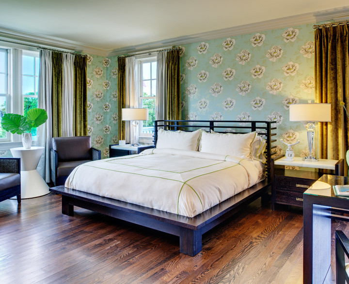 The centerpiece of this luxurious guestroom suite is a latticed–headboard platform bed, flanked by leather–top nightstands and crystal lamps. A pastel, lively printed wallpaper offers pleasing contrast against dark chocolate furniture. Window draperies contrast soft natural silks with heavy velvets. Photo by Christopher Wesnofske