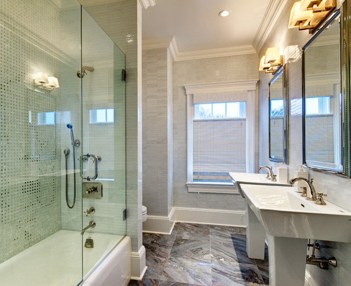 Floor–to–ceiling white glass tile, custom mirrors, glass mosaic shower wall and contemporary pedestal sinks update this Westhampton Beach guest bathroom. The Palisandro Bluette marble floor creates contrast and luxury. Photo by Christopher Wesnofske