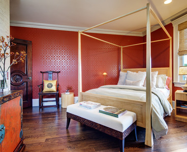 Guests are pampered with a solid bamboo 4–poster bed. Bamboo nightstands mixed with vintage Chinese pieces soften the space and add warmth. The walls are a combination of natural textured grass cloth and patterned red–lacquered paper. Photo by Christopher Wesnofske