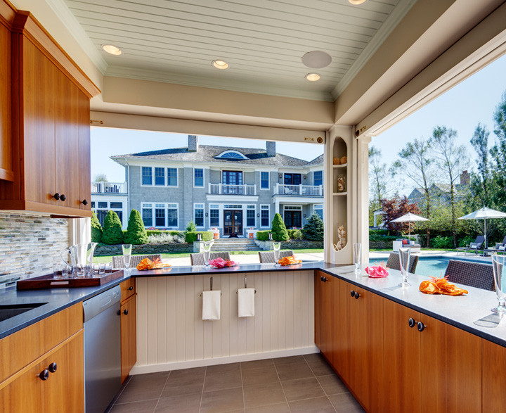 This outdoor kitchen boasts solid teak cabinetry, river stone hardware, and glass backsplash – all perfect for an outdoor setting. Sink, fridge and stove keep the owners from having to run to the house while entertaining or just relaxing poolside. Photo by Christopher Wesnofske