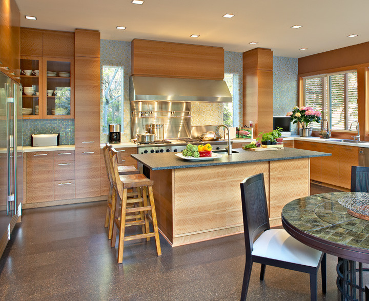 This chef's kitchen was designed for a client who loves to cook. From the large Viking stove to the sea of windows opening to a California pergola, every element was thoughtfully planned. African cedar wood flows horizontally; recycled glass glistens above a sandblasted granite countertop. Recycled cork floor. Photo by Christopher Wesnofske