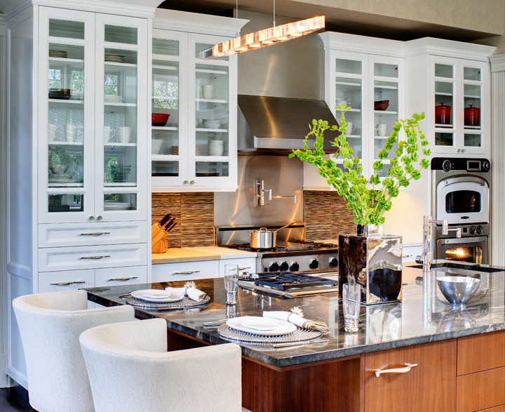 Here's how to dine casually in a luxurious kitchen. Barstools are upholstered with indoor/outdoor fabric for easy maintenance and the exquisite marble island countertop is easily wiped. A Turbo Chef double wall oven, full stove and island cook top with hydraulic vent make casual cooking easy. Photo by Christopher Wesnofske