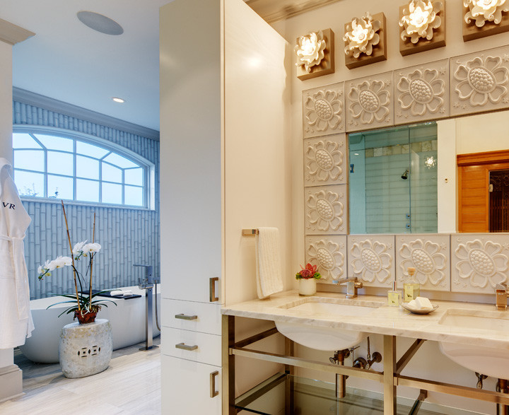 Begin and end each day in pampered luxury. Here, a deep bathtub sits below a sun or moonlit window. White porcelain floral sconces and tile-framed mirror are flanked by custom storage cabinets. The white travertine countertop, repeated on the floor, unifies the space – and the mood. Photo by Christopher Wesnofske