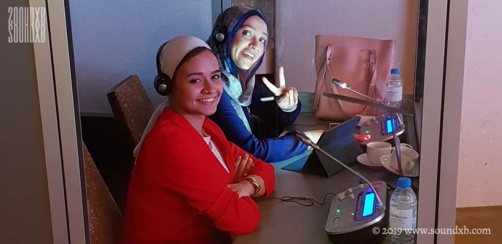 Arabic interpreters smiling in booth Abu