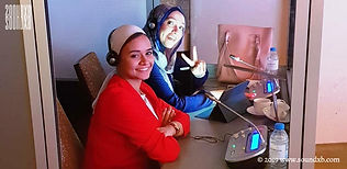 Arabic interpreters smiling in booth Abu