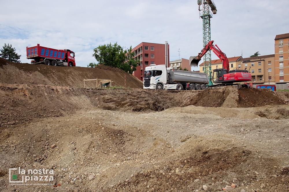 Escavatori e camion in manovra nel cantiere de La Nostra Piazza