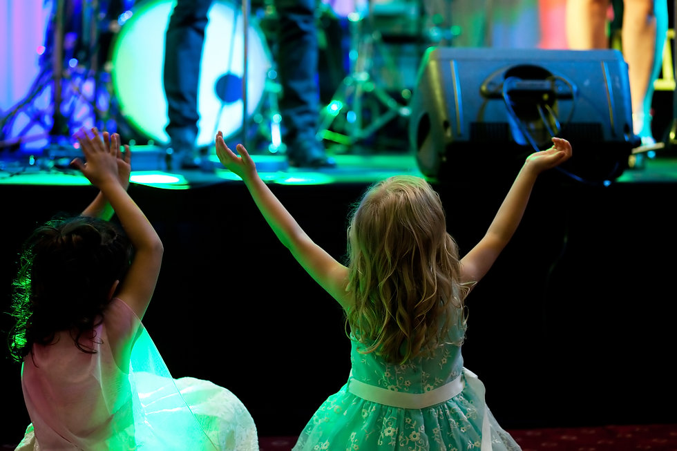 Two little girls in front of stage durin