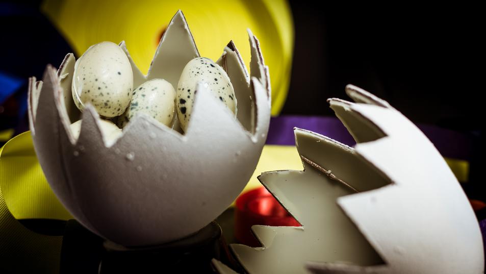 Huevo grande en chocolate blanco y huevos pequeños pintados.