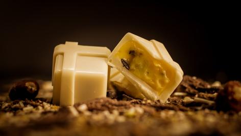 Bombón Belga de Maracuyá, crema de maracuyá bañada en chocolate blanco.