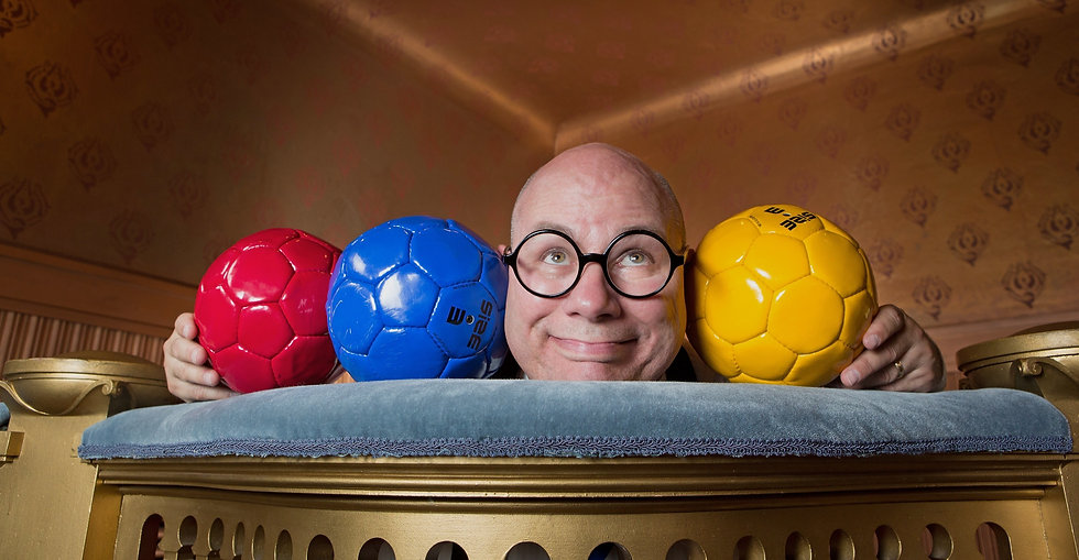 Kenny's bald head is comically squished amongst three soccer balls