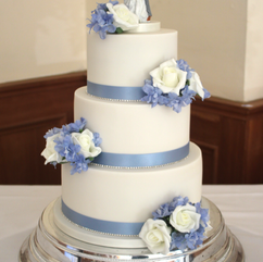 3 tier wedding cake with pale blue ribbon and diamante trim. Decorated with artificial flowers.