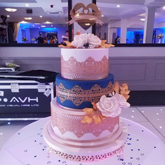 3 tier wedding cake in white and royal blue, decorated with gold edible lace, white sugar roses edged in gold and gold leaves.