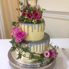 2 tier buttercream wedding cake with silver painted drip effect and fresh flowers