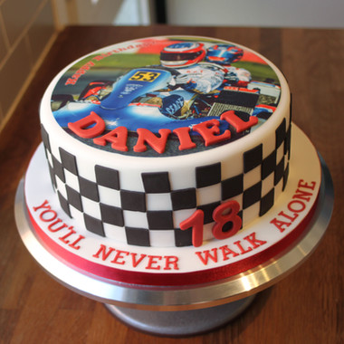 Go cart themed birthday cake with chequered flag decoration and edible printed image.