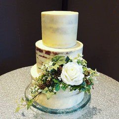 3 tier semi-naked cake with artificial flower arrangement