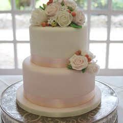 Two tier wedding cake in pale pink and peach tones with sugar roses