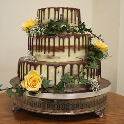 3 tier semi-naked wedding cake with chocolate drip effect and fresh flowers & ivy