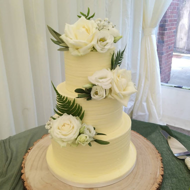 Buttercream wedding cake with fresh roses and greenery