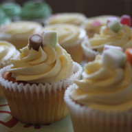 Vanilla cupcakes with a swirl of buttercream decorated with sweets.