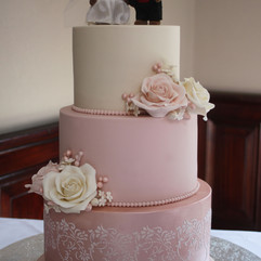 3 tier wedding cake with ivory and pink sugar roses and stencilled design
