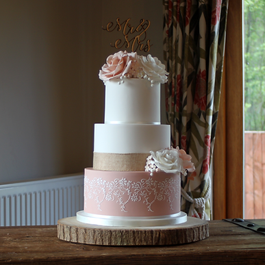Three tier gluten-free wedding cake in white and dusky pink, decorated with stencilling and sugar roses