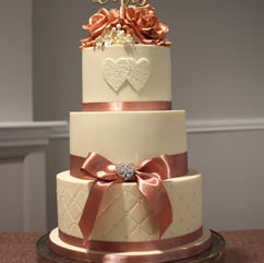 3 tier wedding cake with rose gold sugar roses, embossed hearts and quilted effect
